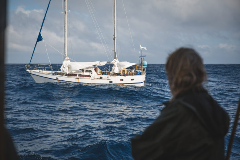 Bemanning van zeilend vrachtschip redt man van zinkende boot