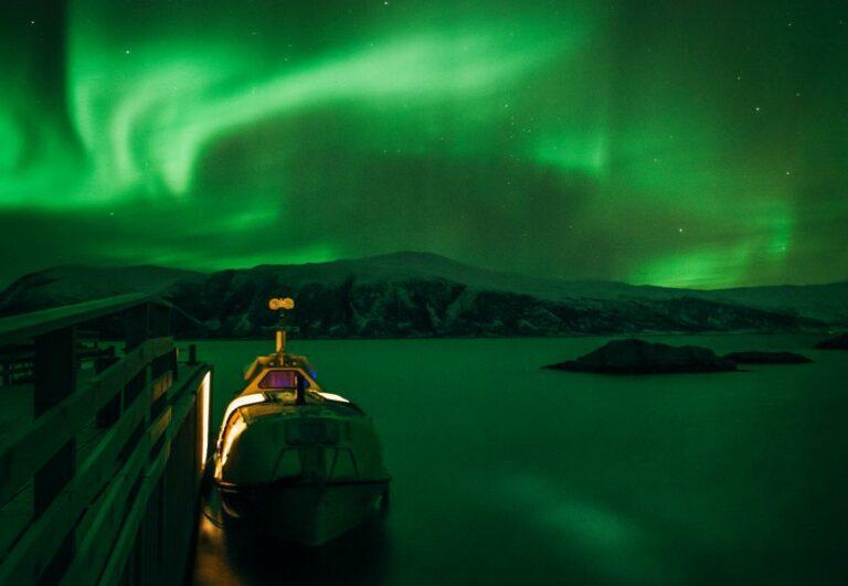 Twee mannen en een hond varen in een lifeboat naar het Noorderlicht
